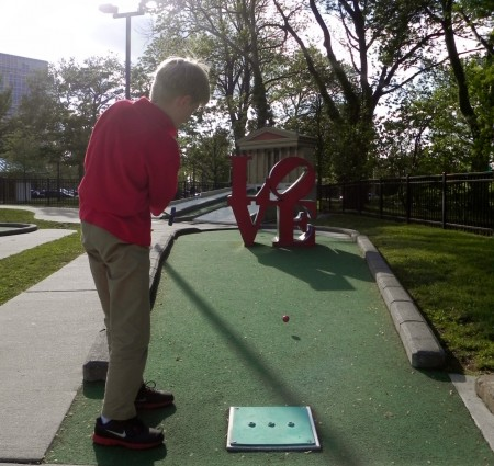 Playing mini golf through the LOVE statue in Philadelphia's Franklin Square